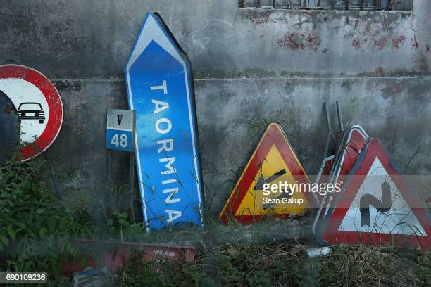 Roadsigns including one for pointing in the direction of the village of Taormina lie next to a building during the G7 Taormina summit on the island...