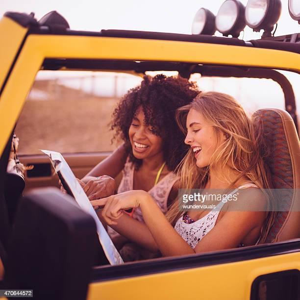 Road-Tropeçar Afro menina e amigo a verificar as direcções num mapa