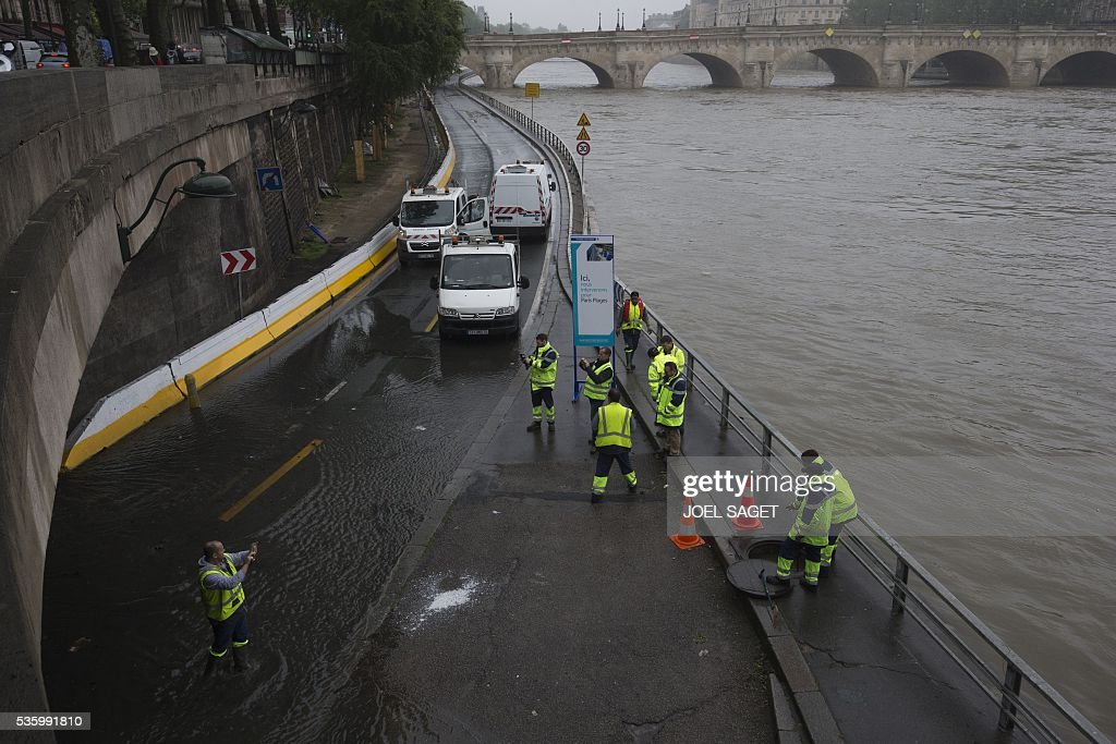 Roadworkers intervene on the expressway by the river Seine near the Pont Neuf after its banks became flooded following heavy rainfalls on May 31, 2016 in Paris. France's weather agency Meteo France maintained today 18 departments under orange alert for heavy rainfalls, which have already disrupted transports in the northeastern part of the country. / AFP / JOEL