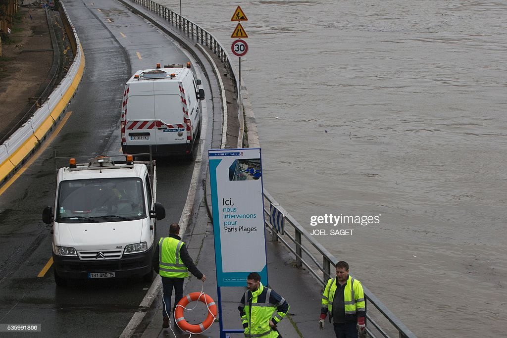 Roadworkers intervene on the expressway by the river Seine near the Pont Neuf after its banks became flooded following heavy rainfalls on May 31, 2016 in Paris. France's weather agency Meteo France maintained today 18 departments under orange alert for heavy rainfalls, which have already disrupted transports in the northeastern part of the country. The placard reads 'We intervene here as part of the upcoming Paris Plages (Paris Beaches) event'. / AFP / JOEL