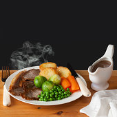 Roast Beef Concept - steaming hot roast beef with roast potatoes, brussels sprouts, carrots, peas and a jug of gravy, on a dark background with the words Roast Beef. This image can be fully customized
