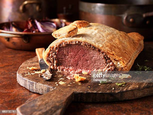 Roast beef wellington, red onions in background, fresh thyme