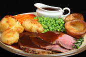 British roast beef dinner with Yorkshire puddings. Shallow DoF, sharp focus at centre of image.