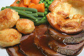 Traditional British roast beef dinner with yorkshire pudding and vegetables