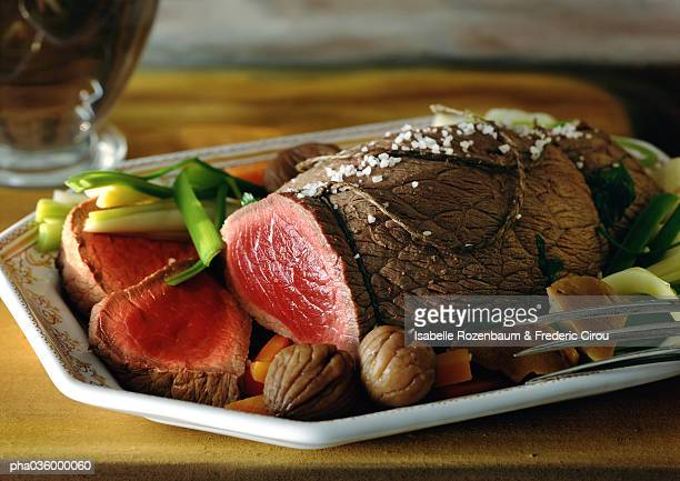 Roast beef with vegetables on dish, close-up