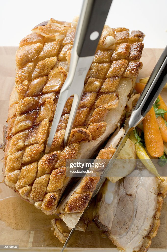 Roast belly pork with crackling and vegetables, close up : Stock Photo