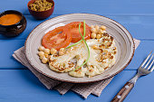 Roast cauliflower steak with tomatoes and chickpeas. Selective focus.