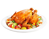 Roast chicken on a plate of vegetables