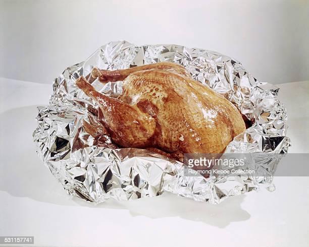 A roast chicken or turkey wrapped in aluminium foil circa 1965
