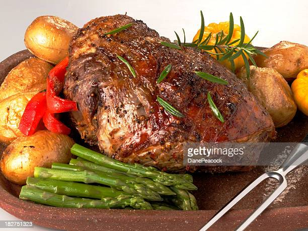Roast leg of lamb surrounded by veggies on wooden tray