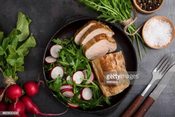 Roast pork fillet with arugula and radish salad