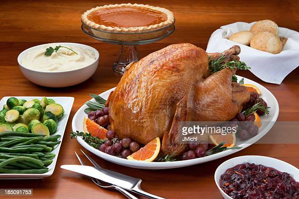 Roast Turkey and Side Dish's on a Cherry Wood Table.