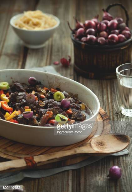 Roasted beef with vegetables and onions in basket on wooden table.