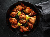 Roasted boneless skinless chicken thighs in lemon and thyme dressing served in vintage cast iron skillet, frying pan.
