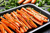 Fried carrots with green herbs in baking tray, close up