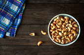 Roasted cashew nuts in a bowl on natural background wooden table