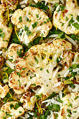 Roasted cauliflower slices of parmesan cheese, parsley and lemon zest, top view