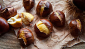 Traditional Christmas dish  - Ripe Sweet Roasted Chestnuts, cracked shells after put to the fire, natural paper and old wooden rustic background.