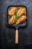Roasted chicken breast in grill pan with fresh herbs and spices  on dark rustic background, top view
