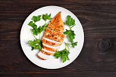 Roasted chicken breast decorated with parsley on white plate over wooden background, top view