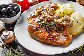 roasted Chicken Breast with Mushroom Sauce and mashed potato in white plate on dark background