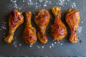 Roasted chicken drumsticks on black background. Cooked with sauce from mustard and olive oil. Top view.