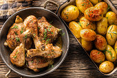 Roasted chicken legs with potatoes cumin pepper and herbs top of view.