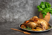 Roasted chicken, potatoes and vegetables in plate on grey background. Side view. With copy space.
