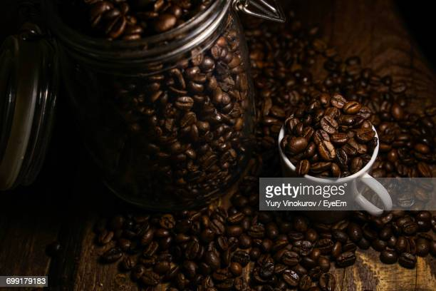 Roasted Coffee Beans In Glass Jar And Cup On Table