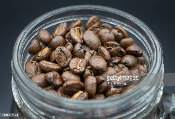 Roasted coffee beans in the glass mug.