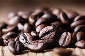 Roasted coffee beans on wooden background. Close-up shot.