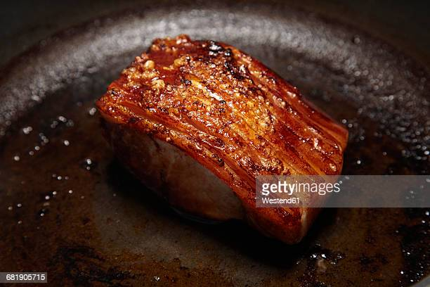 Roasted, crisp pork saddle in frying pan