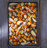 Roasted root vegetables on a baking sheet: sweet potato, butternut squash, brussels sprouts, apple, pecans and pear. Toning. Healthy eating concept.
