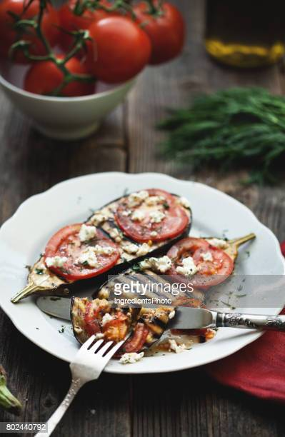 Roasted eggplant with tomatoes and cheese on a wooden table.