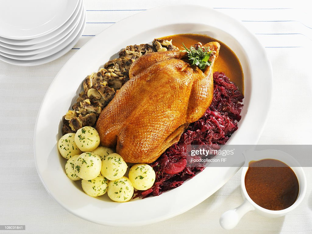 Roasted goose garnished with red cabbage and dumplings : Stock Photo