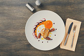Roasted goose liver with date and apple, fruit and berry sauce painting and cutlery top view. Creative french cuisine, delicatessen restaurant meal