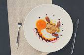 Roasted goose liver with date and apple, fruit and berry sauce painting with cutlery top view. Creative french cuisine, delicatessen restaurant meal