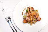 Roasted Pheasant on a bed of Vegetable on a white plate. Room for copy