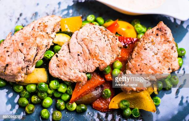Roasted pork meat fillet chops with zucchini, onion, yellow and orange bell pepper, frozen peas on a plate with cream sauce, top view