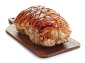 roasted pork on wooden cutting board isolated on white background