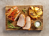 roasted pork slices and potatoes on wooden cutting board, top view