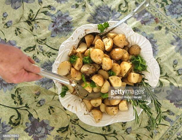 Roasted potatoes are scooped out of a bowl at a free community dinner at Fryeburg Academy in Freyburg on Tuesday August 25 2015 Green Thumb Farms...