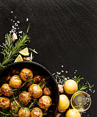 Roasted potatoes with rosemary, garlic, lemon and sea salt on a black background. Vegetarian dish nutritious and delicious