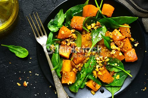 Roasted pumpkin salad with spinach and walnut .Top view. : Stock Photo