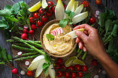Plate of roasted radishes hummus with raw vegetables
