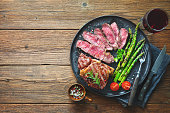 Roasted rib eye steak with green asparagus and wine on wooden table