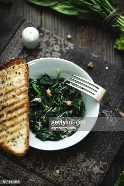Épinards avec de l'ail rôti et parmesan sur une table en bois.