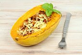 Spaghetti squash with a fork,  cheese and basil on the top