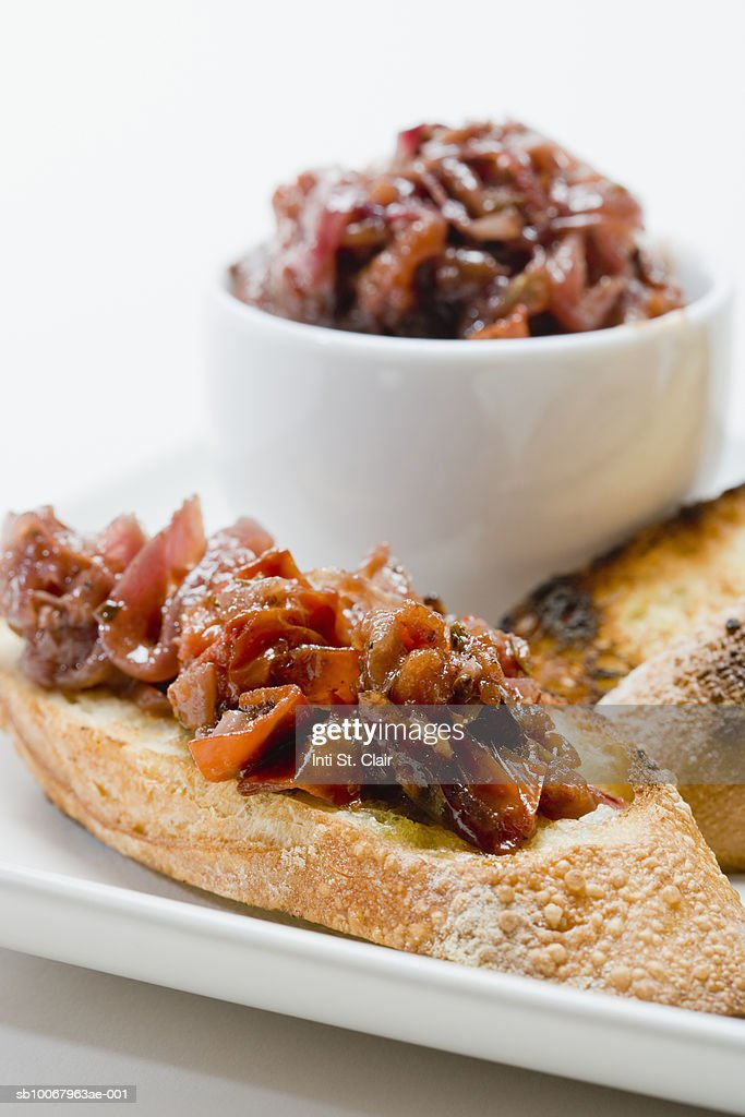 Roasted tomato and onion relish on crostini on plate, close up. studio shot