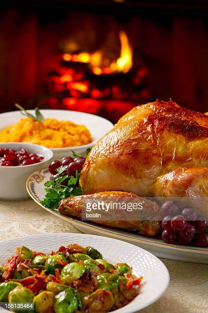 A roasted turkey with side dishes with a fire
